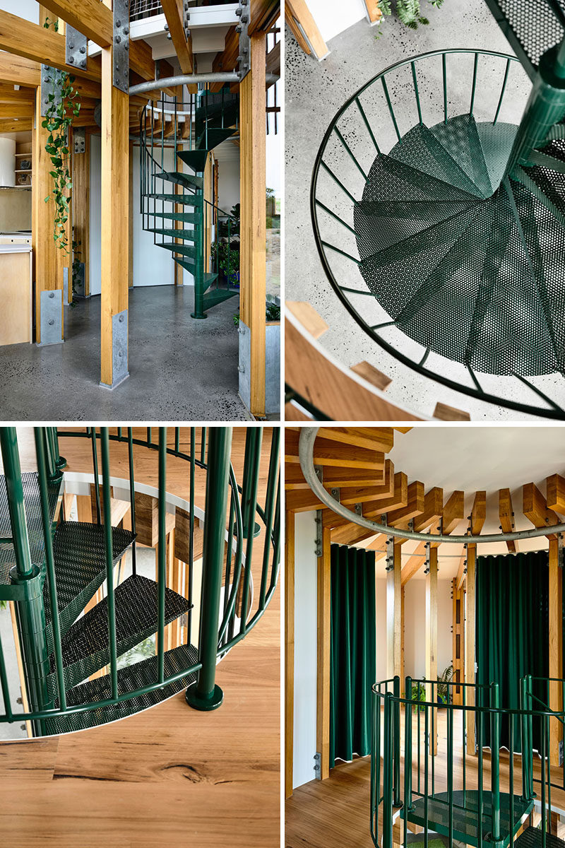 A dark green metal spiral staircase connects the two floors of this modern circular beach house. #SpiralStairs #SpiralStaircase