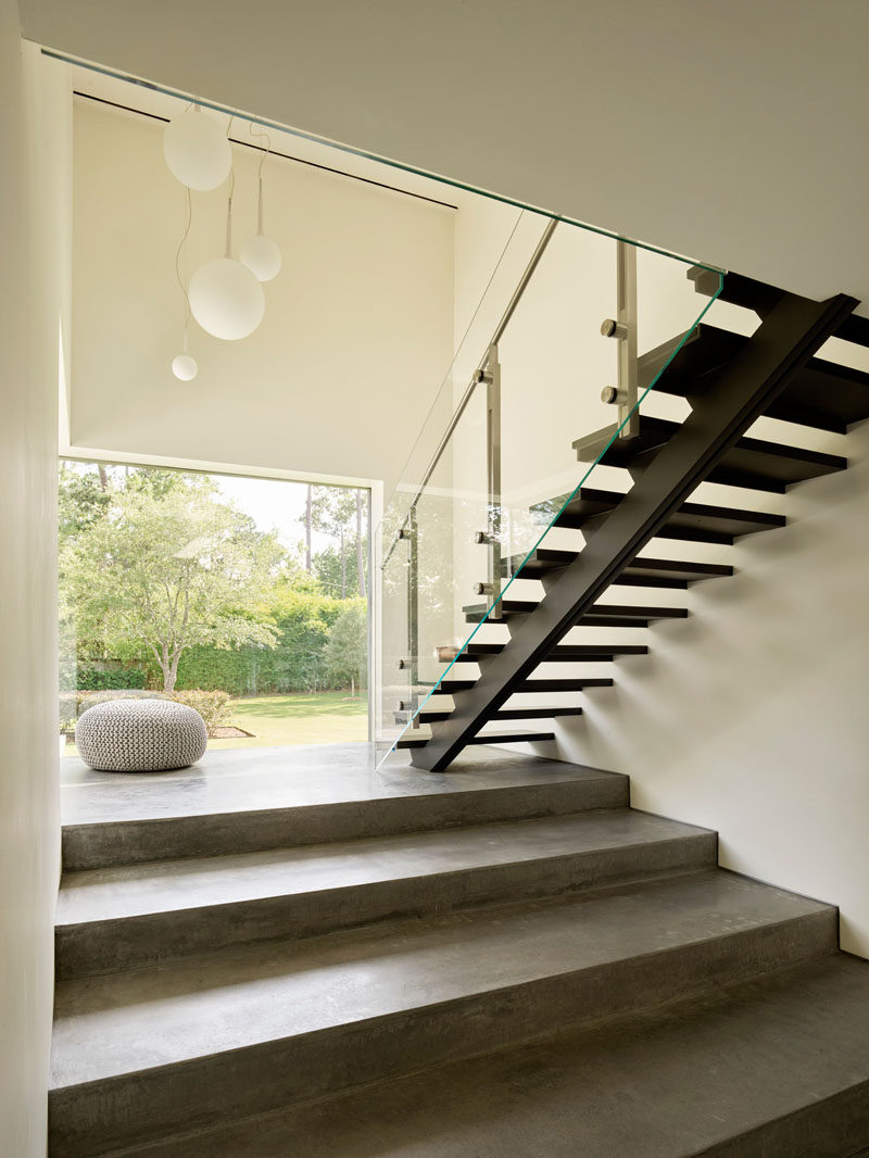 This modern staircase provides a contrast in materials, commencing from the ground plane as three broad concrete amphitheater steps, then transforming into black steel treads and glass as it ascends further. #ModernStairs #Staircase