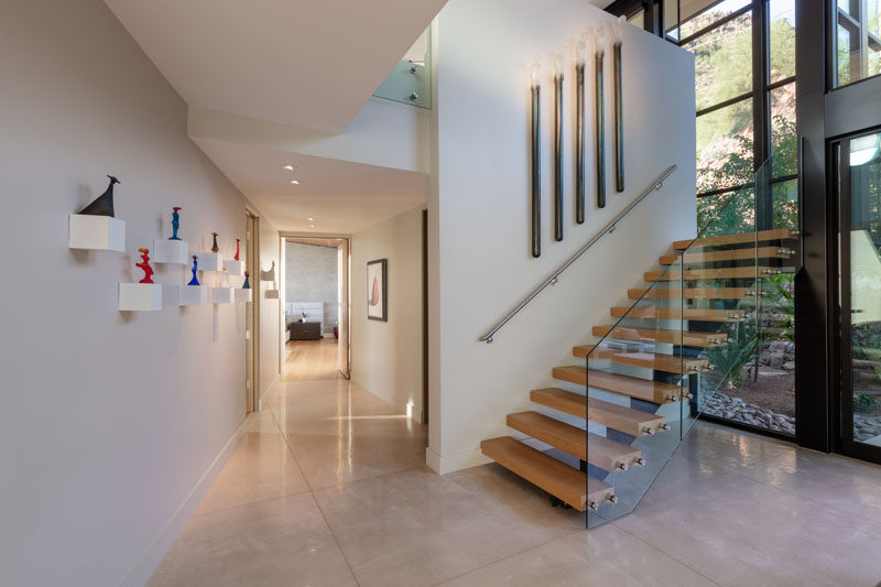 This modern house has wood and steel stairs with a glass handrail, that lead up to the second floor of the home. #ModernStairs #StairDesign