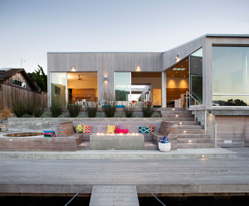 The wood deck of this modern house has various levels and seating options, and leads down to a private dock. #Deck #OutdoorFire #OutdoorLounge