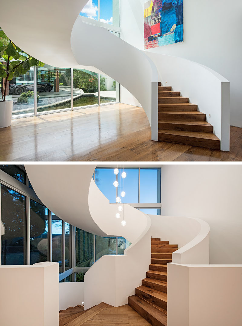 A grand spiral staircase with wood treads, leads to the upper floors of this modern house. #Stairs #SpiralStairs