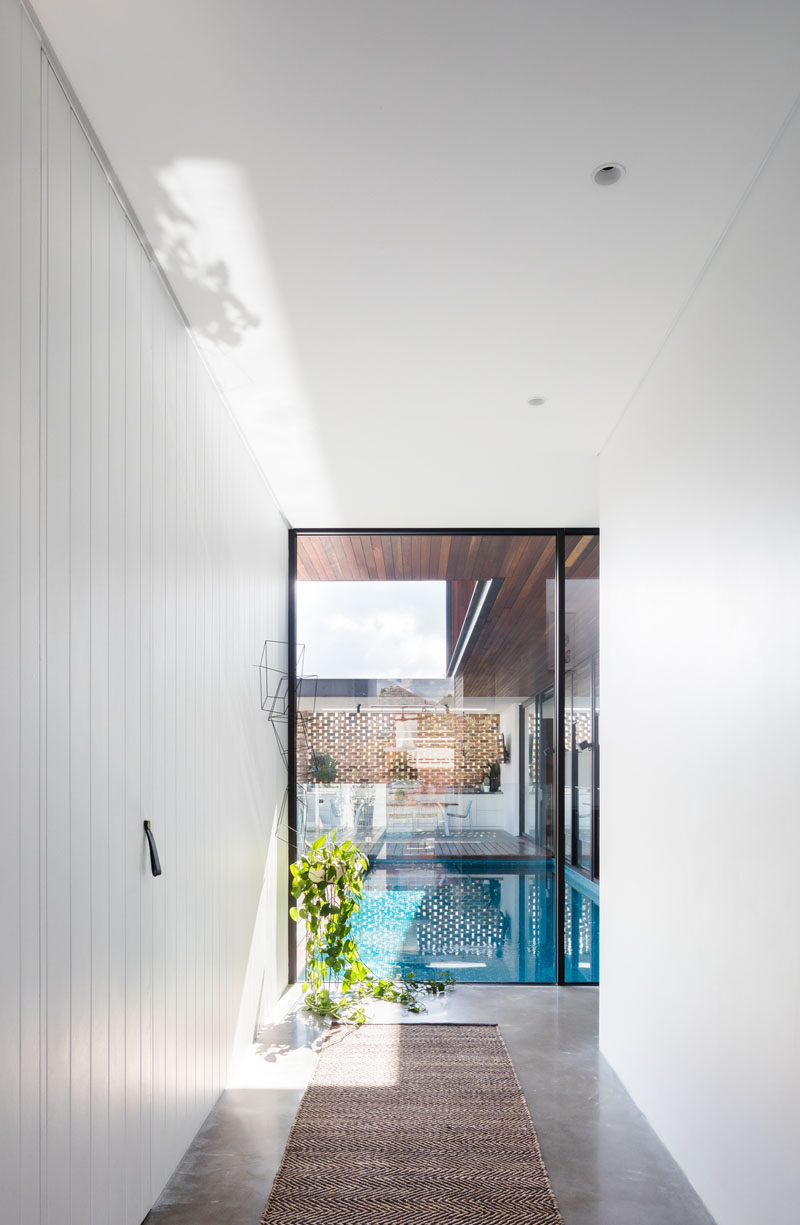 Inside this modern house, a hallway with bright white walls leads from the entryway towards the pool and social areas of the house. #InteriorDesign #Hallway #Windows