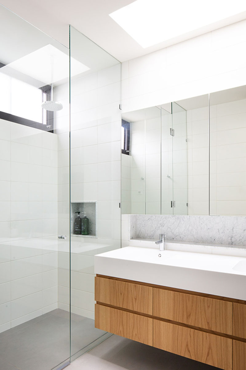 In this modern bathroom, a skylight helps to keep the white bathroom bright, while a wood vanity adds a natural touch. #ModernBathroom #BathroomDesign