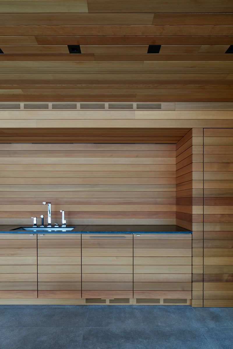 This modern pool house features a wood lined kitchen area with a dark grey countertop. #Kitchen #WoodKitchen #ModernKitchen