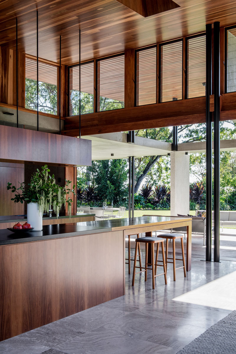 Sliding glass walls open the interior of this modern house to the backyard, creating an indoor/outdoor living environment. #WoodKitchen #InteriorDesign #KitchenDesign