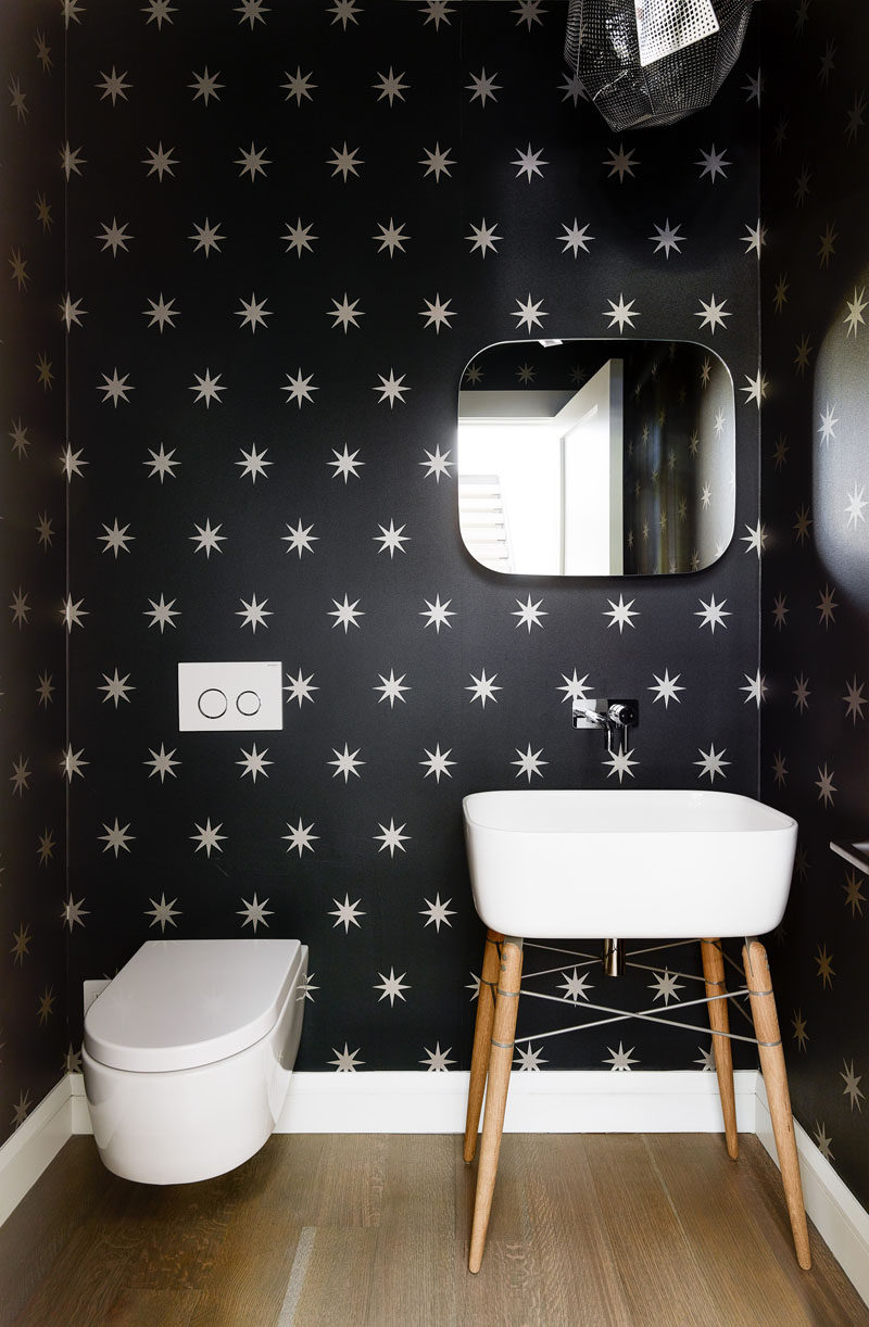 In this modern bathroom, black and white wallpaper covers the walls to a create a fun and unexpected look. #SmallBathroom #BathroomDesign