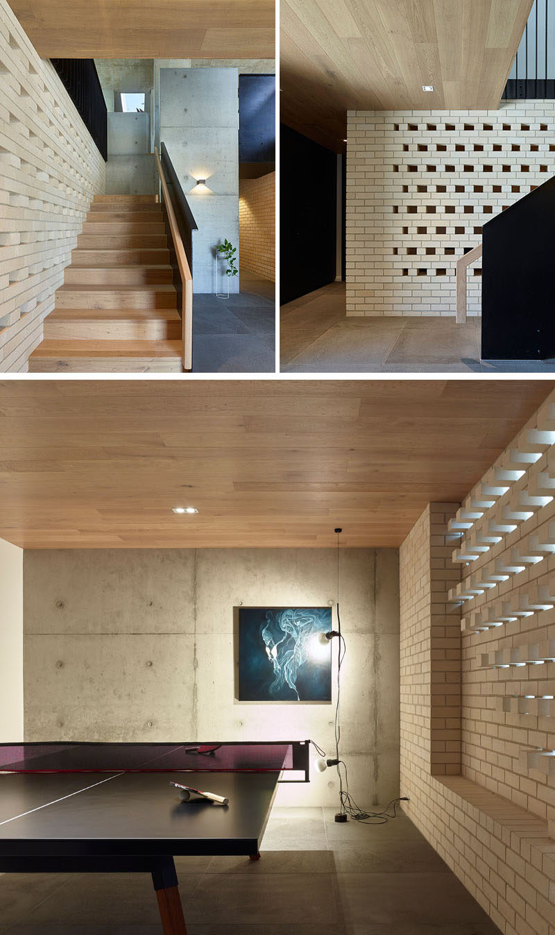 This modern house has stairs that run alongside a white brick wall, leading down to the front door, the garage, and a games room. #WhiteBricks #GamesRoom #Stairs