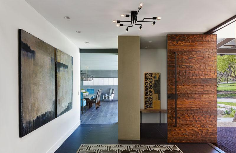 A large pivoting wood front door welcome visitors to this modern house. #FrontDoor #WoodFrontDoor