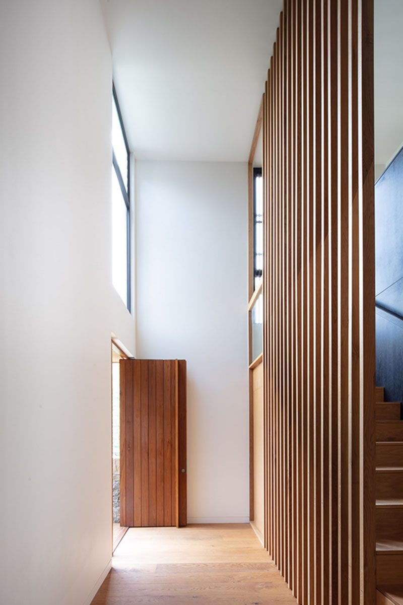The wood front door opens up to a double height entryway that guides guests to the hallway leading to the social areas of this modern house. #WoodFrontDoor #FrontDoor