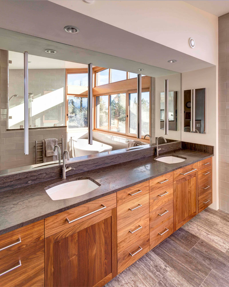 In this contemporary bathroom, a large mirror reflects the light from the window and views of the valley, while wood cabinets and a stone counter bring a natural touch to the interior. #BathroomDesign #ContemporaryBathroom