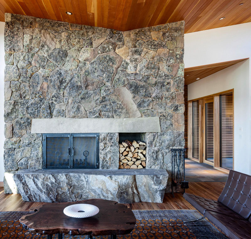 A single slab of stone serves as the hearth and another as the mantle to this contemporary house's wood-burning fireplace. #Fireplace #StoneFireplace #LivingRoom