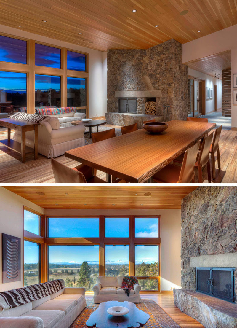 The open-plan interior of this contemporary home features natural materials, a dining area with a sustainably harvested Sapele wood dining table sporting its live edge, and wood floors throughout the home that came from hardwoods salvaged from shipping crates. #LivingRoom #DiningRoom #StoneFireplace