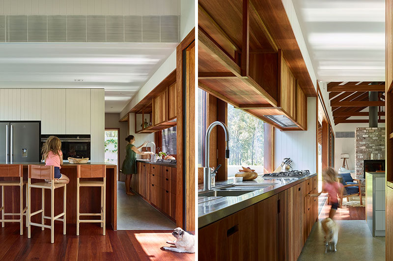 In this modern kitchen, simple wood cabinets line the wall, while the windows act as a backsplash behind the cooktop and sink. #ModernKitchen #WoodKitchenCabinets