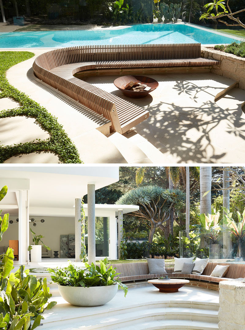 This modern backyard features a swimming pool and a large, curved, slightly sunken, built-in wood slat seat that focuses on the fire bowl. #Landscaping #OutdoorSeating #SwimmingPool #Backyard