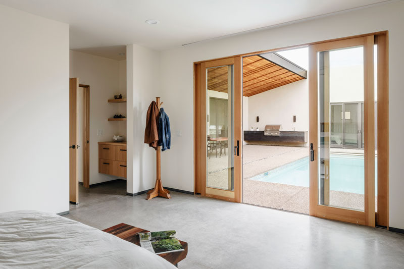 Wood-framed, sliding glass doors connect the courtyard of this modern house to the master bedroom. #SlidingGlassDoors #SlidingDoors #Doors