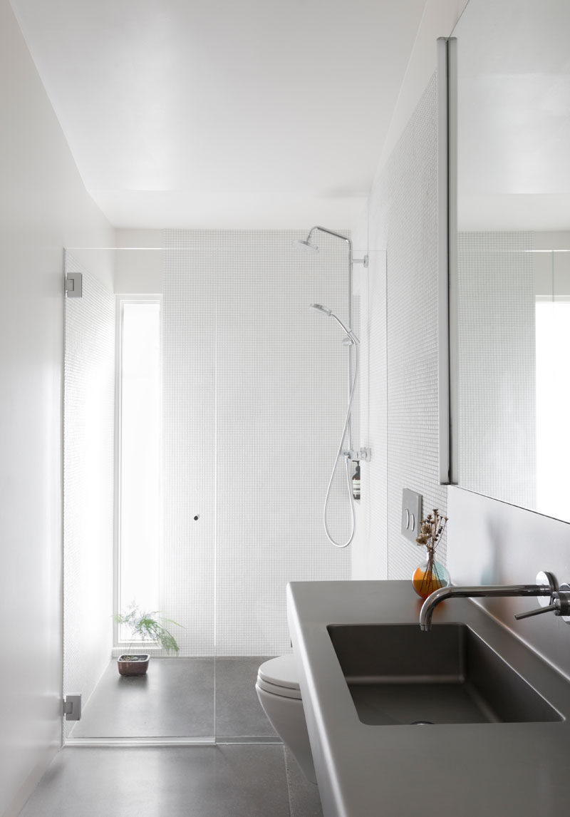 This bathroom received a fresh and modern update, with bright white walls and a window in the shower, adding extra light to the room. #ModernBathroom #BathroomDesign