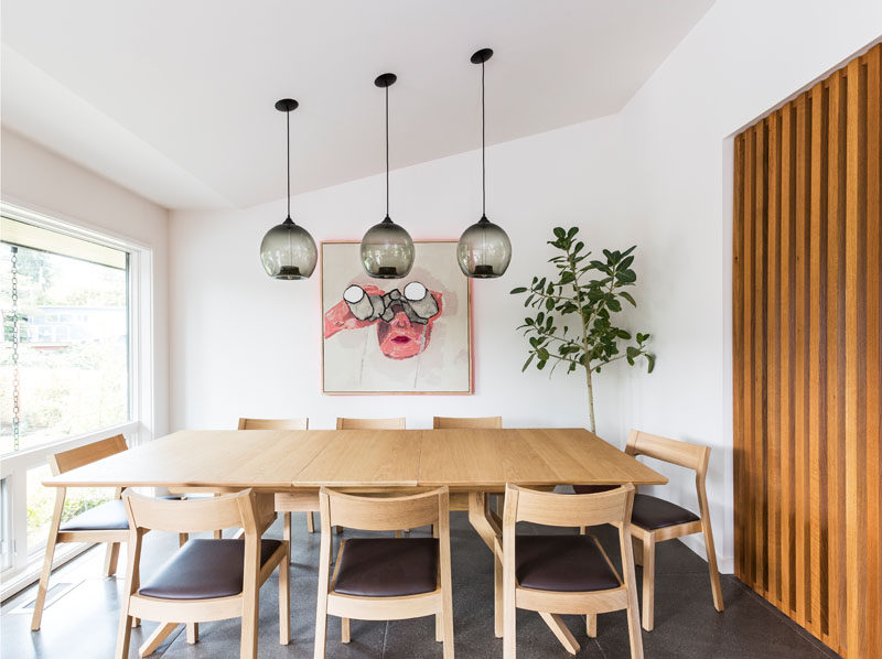 This modern dining room has three simple black glass pendant lights hanging above the table. A pop of color has been added to the wall in the form of a painting. #DiningRoom #ModernDiningRoom