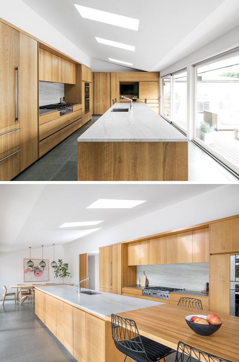 SHED transformed and updated the kitchen in an old ranch house and inserted an oversized kitchen island that takes a commanding position in thespace, while providing ample room to cook, eat, and socialize. #ModernKitchen #LargeKitchenIsland #WoodKitchenCabinets