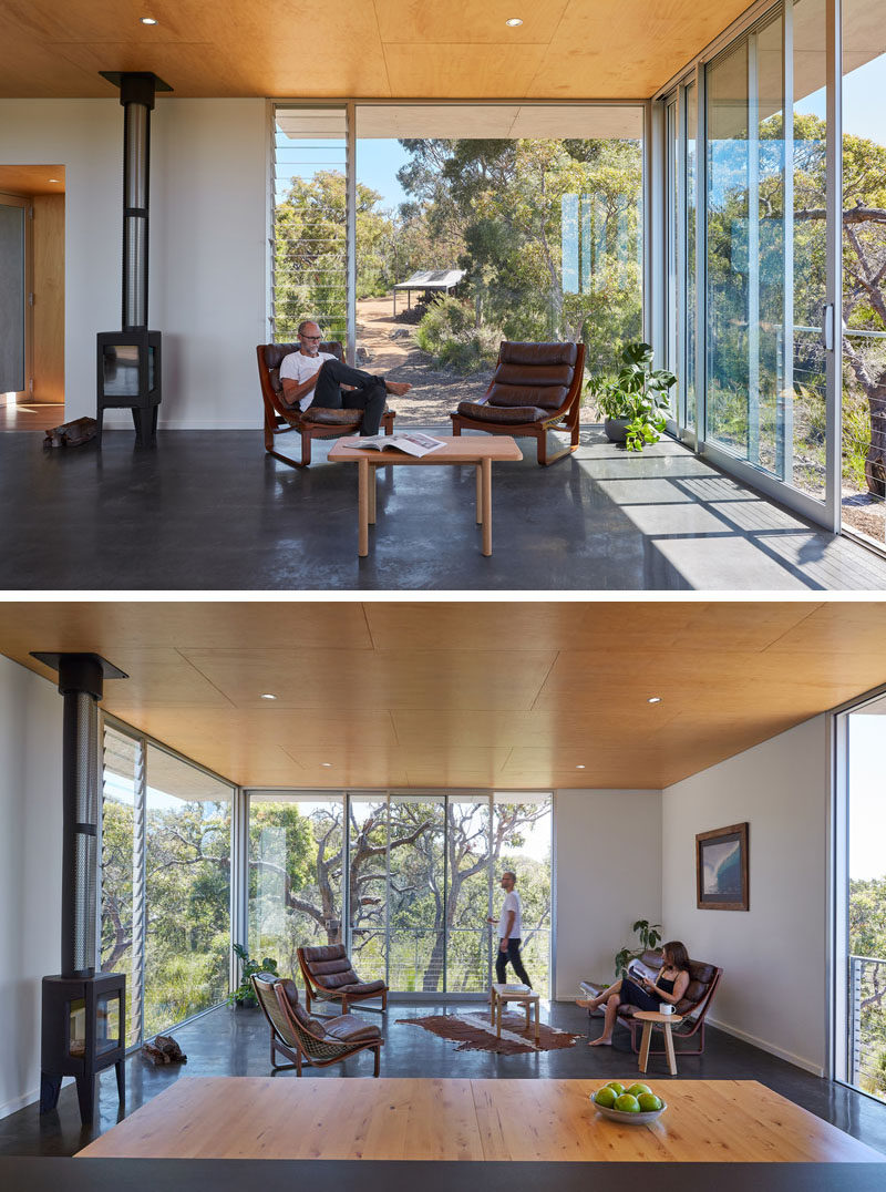Inside the main floor of this modern house, pine plywood sheets cover the ceiling, while large areas of glass can be slid open toevoke the feeling of being on an open platform up amongst the treetops. #WoodCeiling #LargeWindows #LivingRoom