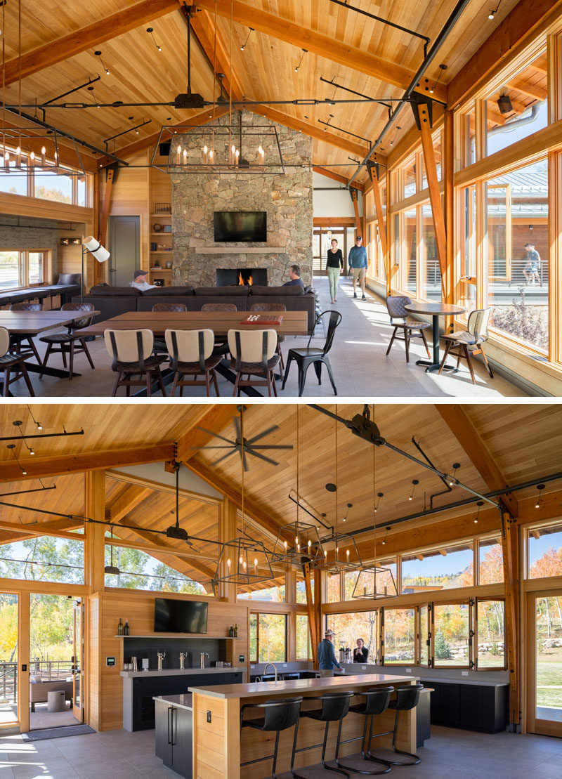 Created to be the vibrant heart of the community at this Colorado ranch, the interior of the activity center features plenty of seating, including a lounge area, games tables, and window seats, as well as a stone fireplace and a bar. #StoneFireplace #Architecture #Bar