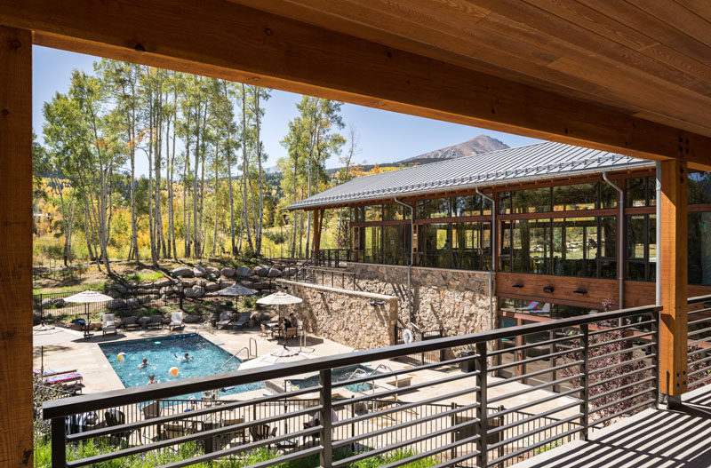 This activity center at a Colorado ranch has covered balconies that provide a view of the swimming pool, spa, and outdoor seating areas below. #SwimmingPool #StoneWalls