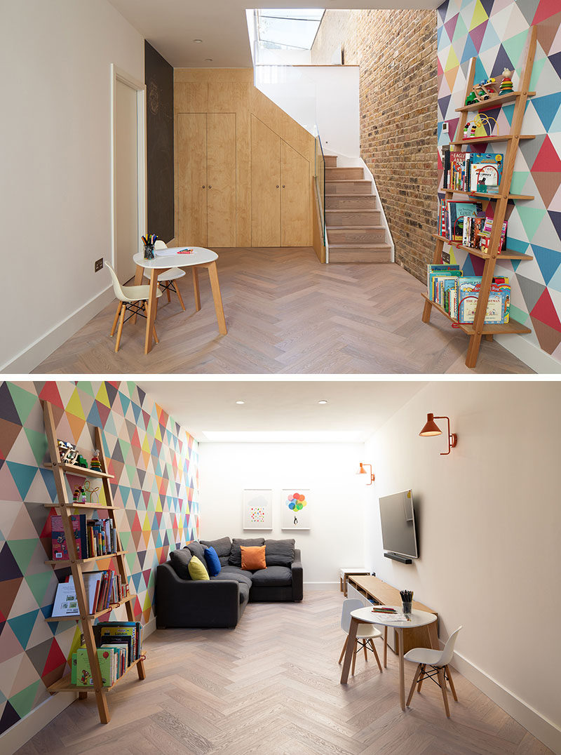 In this modern basement, a brightly colored wall creates a sense of fun, while additional storage has been hidden under the stairs. #ModernBasement #InteriorDesign #Playroom