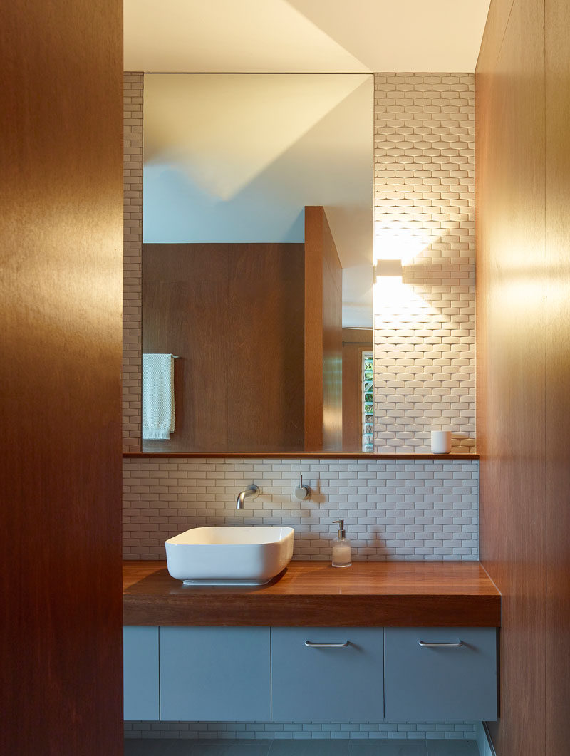 In this modern bathroom, white tile helps to keep the bathroom bright and at the same time adds texture to the wall. #BathroomDesign