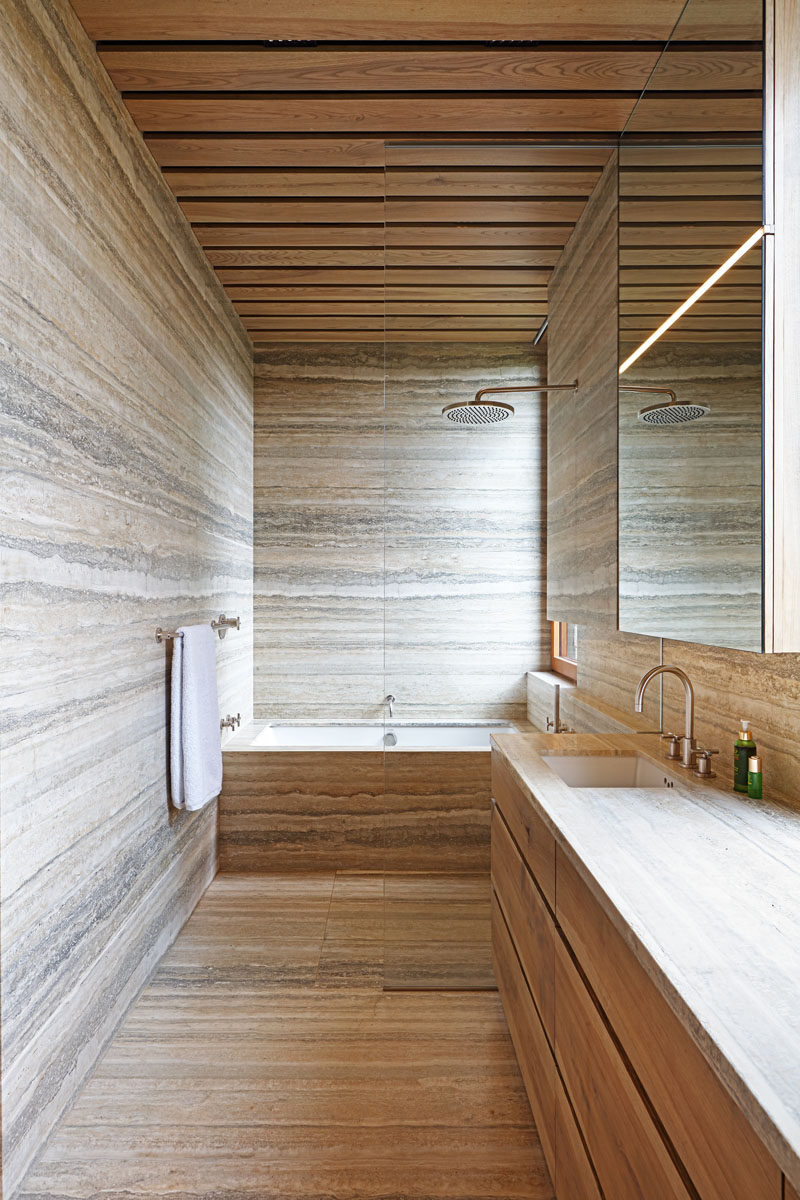 In this modern bathroom, stone covers the floors and walls, while wood has been used for the ceiling and vanity. #BathroomDesign