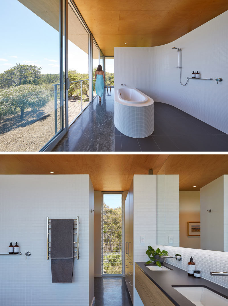 This modern bathroom opens directly onto north facing sliding doors, allowing the home owners to bathe in winter sunshine, while a curved, white mosaic tiled wall acts to softly define this open room and is mirrored in the curved surround to the bath. #ModernBathroom #BathroomDesign