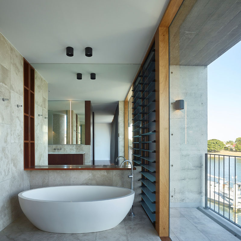 This modern bathroom has a white freestanding bathtub positioned to take advantage of the water views. #Bathroom #Bathtub