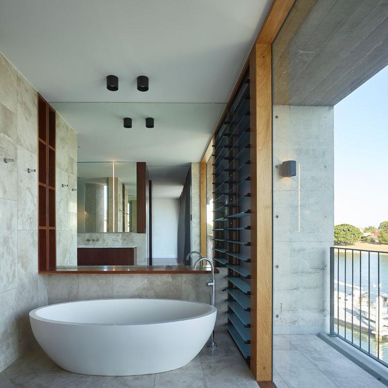 This modern bathroom has a white freestanding bathtub positioned to take advantage of the water views. #Bathroom #Bathtub