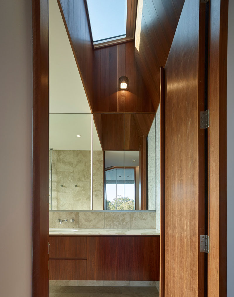 Skylights add natural light to the interior of this modern house, and the angled lines are highlighted by the use of wood. #Skylight