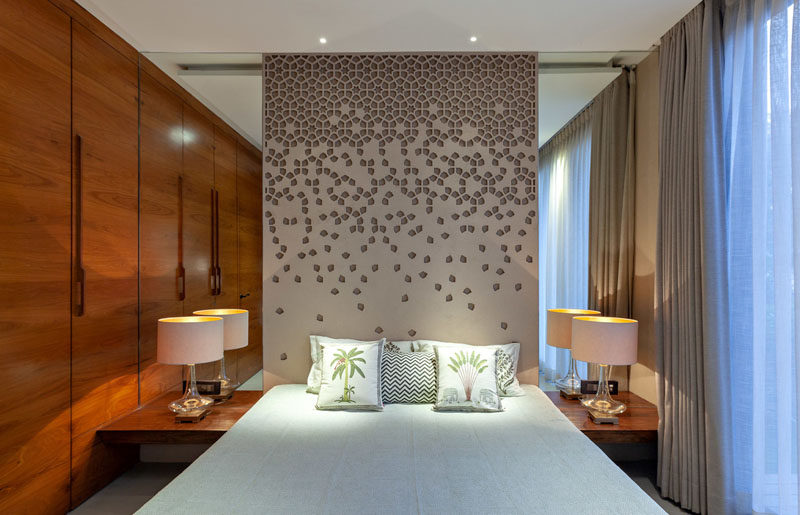 In this modern bedroom, a decorative panel is used as a headboard and mirrors on either side makes the room feel larger. #Bedroom #ModernBedroom