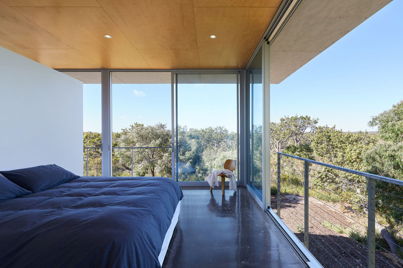 In this modern bedroom, raw galvanised steel Juliet balconies allow the floor-to-ceiling sliding glass doors to be fully openedup to the outdoors. #Bedroom #SlidingGlassDoors #JulietBalcony