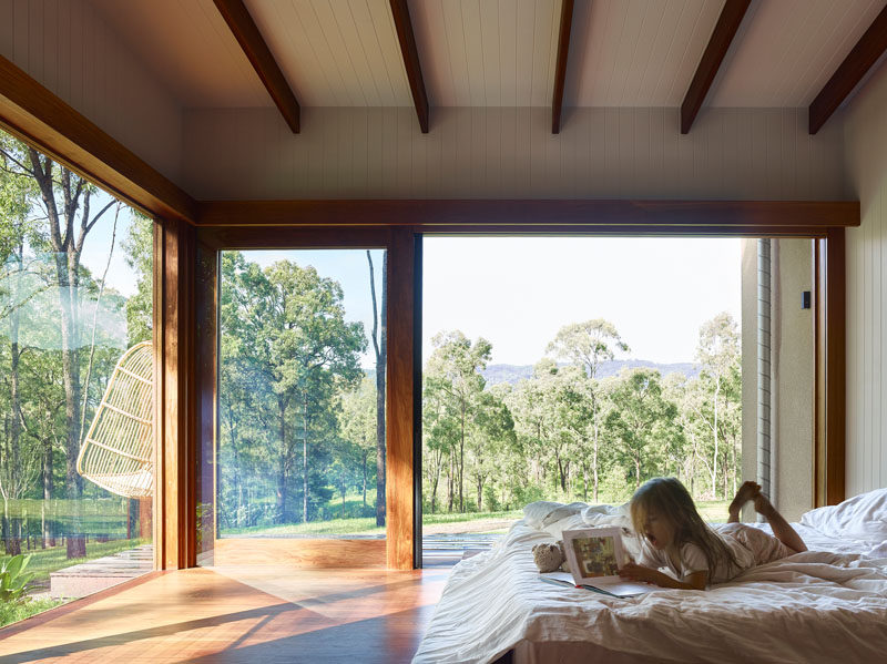 In this bedroom, wood beams draw the eye upwards to ceiling, creating a sense of height, while large windows flood the room with natural light. #Bedroom #LargeWindows