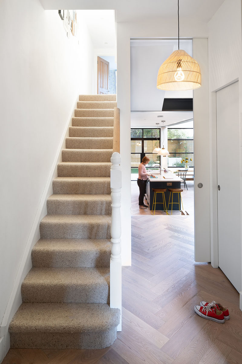 In the entryway of the home, there's a tall pocket door that opens to reveal the new extension. #PocketDoor