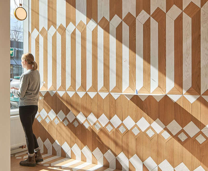This modern coffee shop has a fun and bright geometric pattern on the walls, floor, and ceiling, made from white-washed wood and natural wood. #CoffeeShop #Cafe #InteriorDesign #RetailDesign