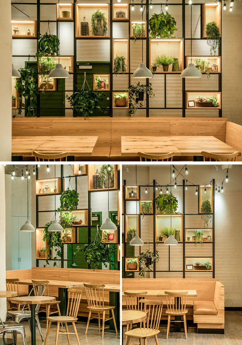 This modern restaurant features wood and leather banquette seating in Garret Glazed bourbon, that's juxtaposed by a wall of live plants hanging in woven cane and wood boxes. #RestaurantDesign #ModernRestaurant #BanquetteSeating #Shelving