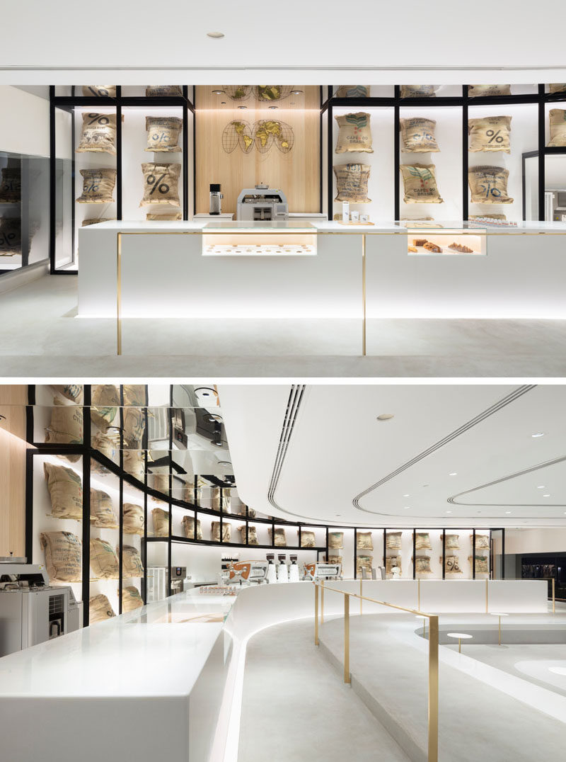 "The design of this modern coffee shop has white coffee machines that almost disappear to the background in order to highlight the coffee beans presented in linen bags behind a glass case and the ""beans map"" element hanged next to it. #CoffeeShop #InteriorDesign"