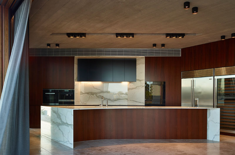 This modern wood and stone kitchen has a large curved island, and is open to both the courtyard and the waterfront, creating true indoor/outdoor living experience. #WoodKitchen #CurvedKitchenIsland