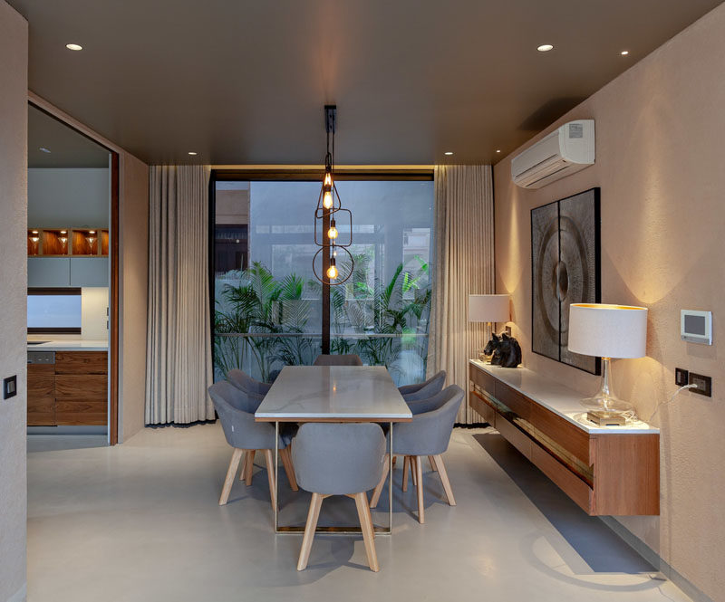 This modern dining room features minimalist lighting above the dining table, while a floating sideboard sits below artwork, and large windows provide a view of the plants outside. #DiningRoom