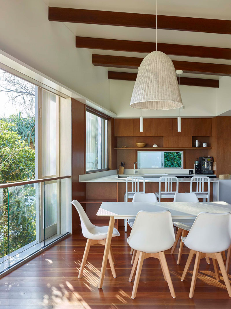 This open plan dining area features a white dining table that complements the white kitchen countertops. #InteriorDesign #DiningRoom #Kitchen