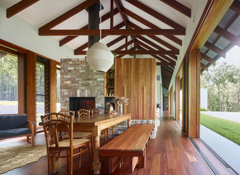 Louver windows and sliding doors allow the breeze to flow through the interior of this modern farmhouse, keeping it cool. #ModernFarmhouse #InteriorDesign
