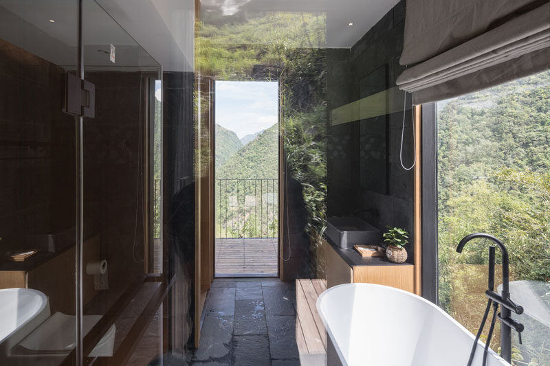 In this holiday cabin, the modern bathroom has a dark interior with a white freestanding bathtub positioned next to the window. #BathroomDesign #DarkBathroom #ModernBathroom