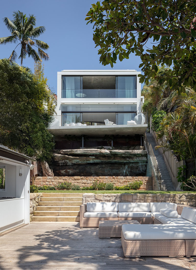 As this modern house sits on a sloped lot, there are stairs located on the side of the house, that connect to a tiered backyard with an outdoor lounge area close to the harbor. #ModernHouse #Landscaping #OutdoorLounge