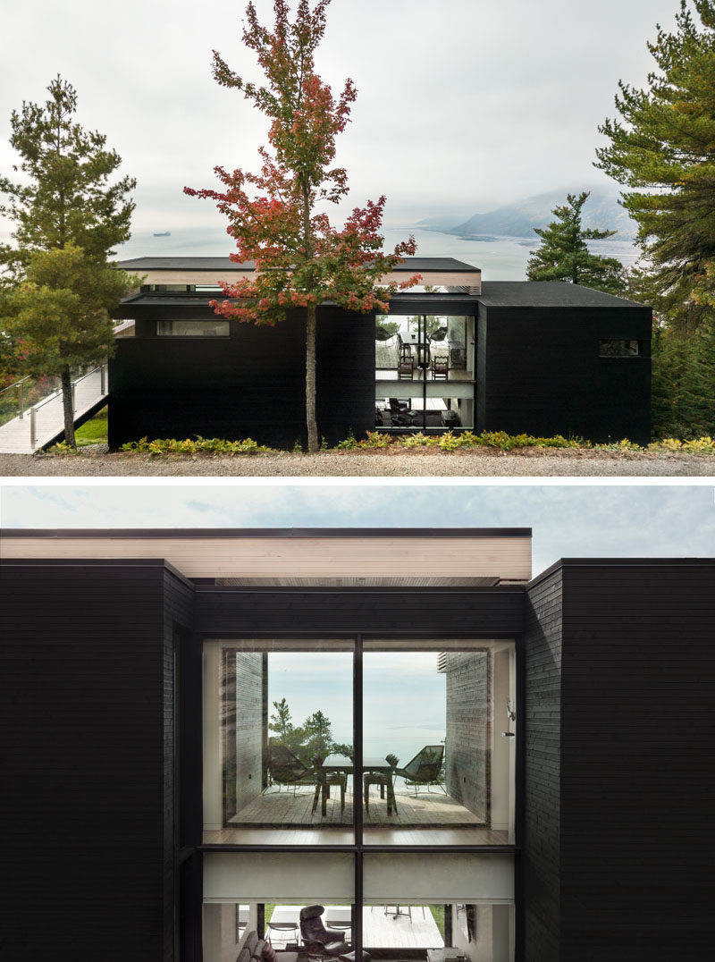 Upon arriving at this modern home, mature vegetation surrounds the house and the dark exterior of the home blends into the color of the bark of nearby trees. #ModernHouse #Architecture #Windows