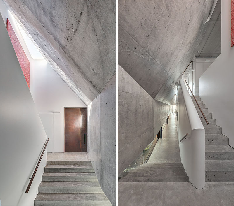 Stepping inside this modern house, there's a series of volumes defined by concrete and white walls. #ConcreteStairs #ModernHouse