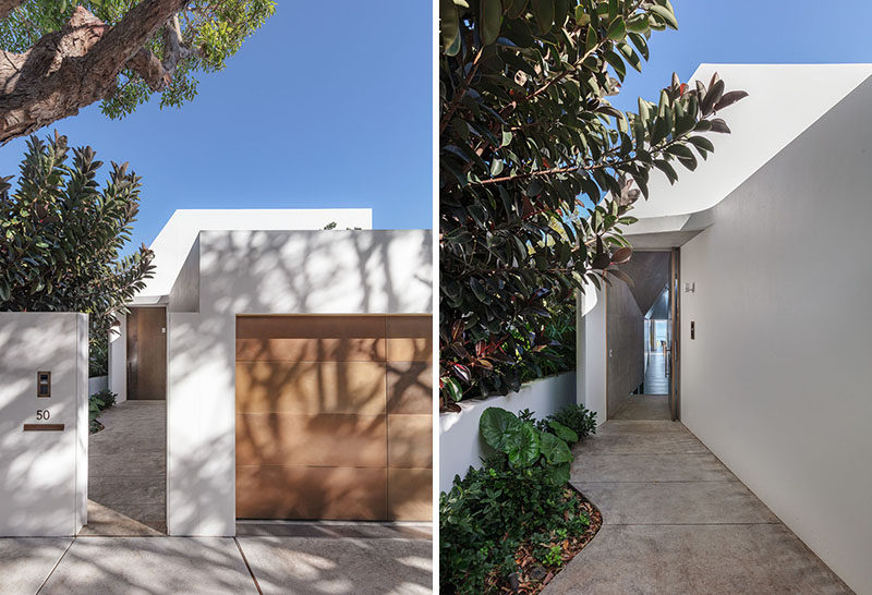 A path leads from the street to the front door of this modern white house. #Landscaping #Path