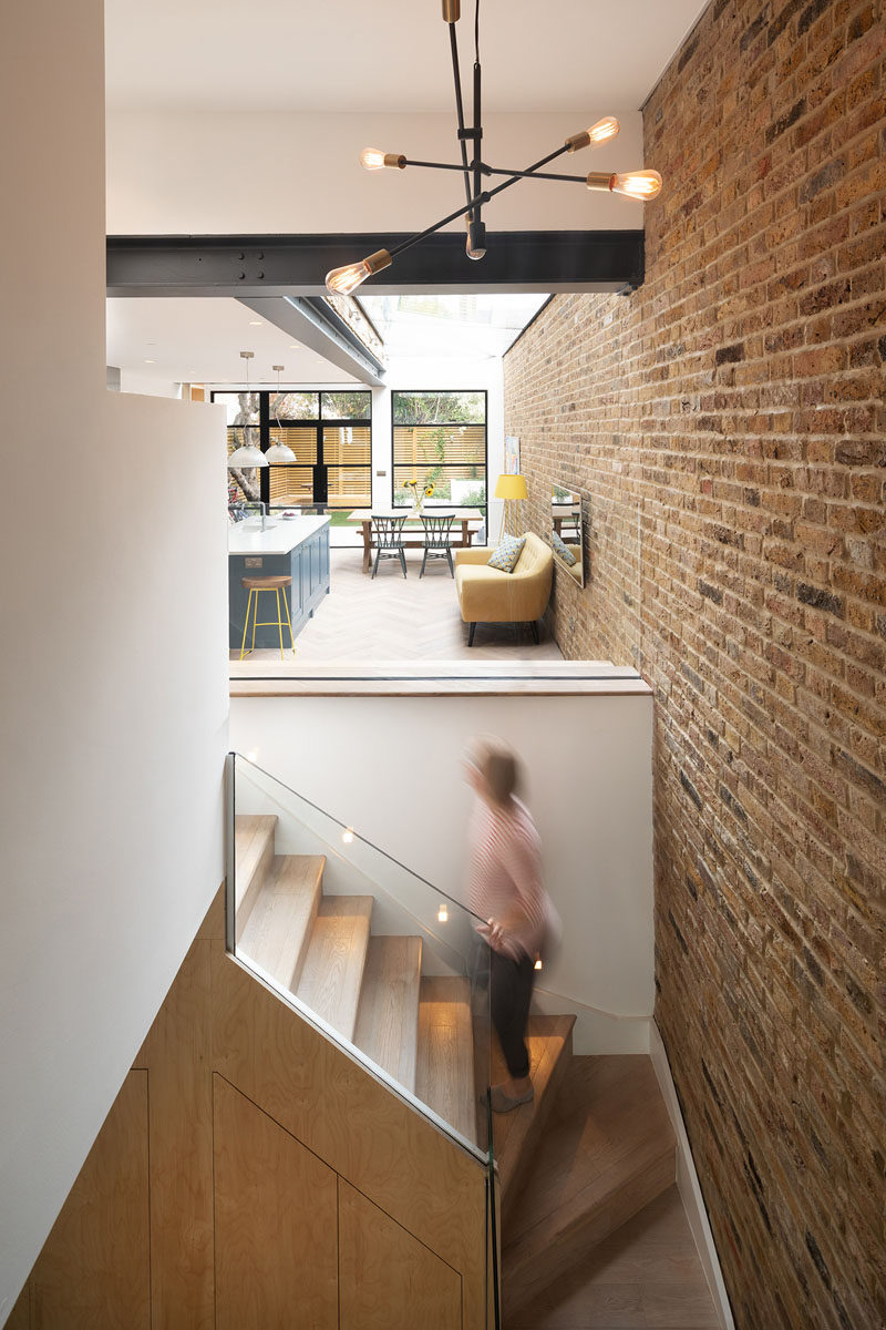 In this house, wood stairs connect the new extension to the basement downstairs, and from this angle, you can see the large metal beams that contrast the white walls and ceiling. #Stairs #HouseExtension #ModernInterior