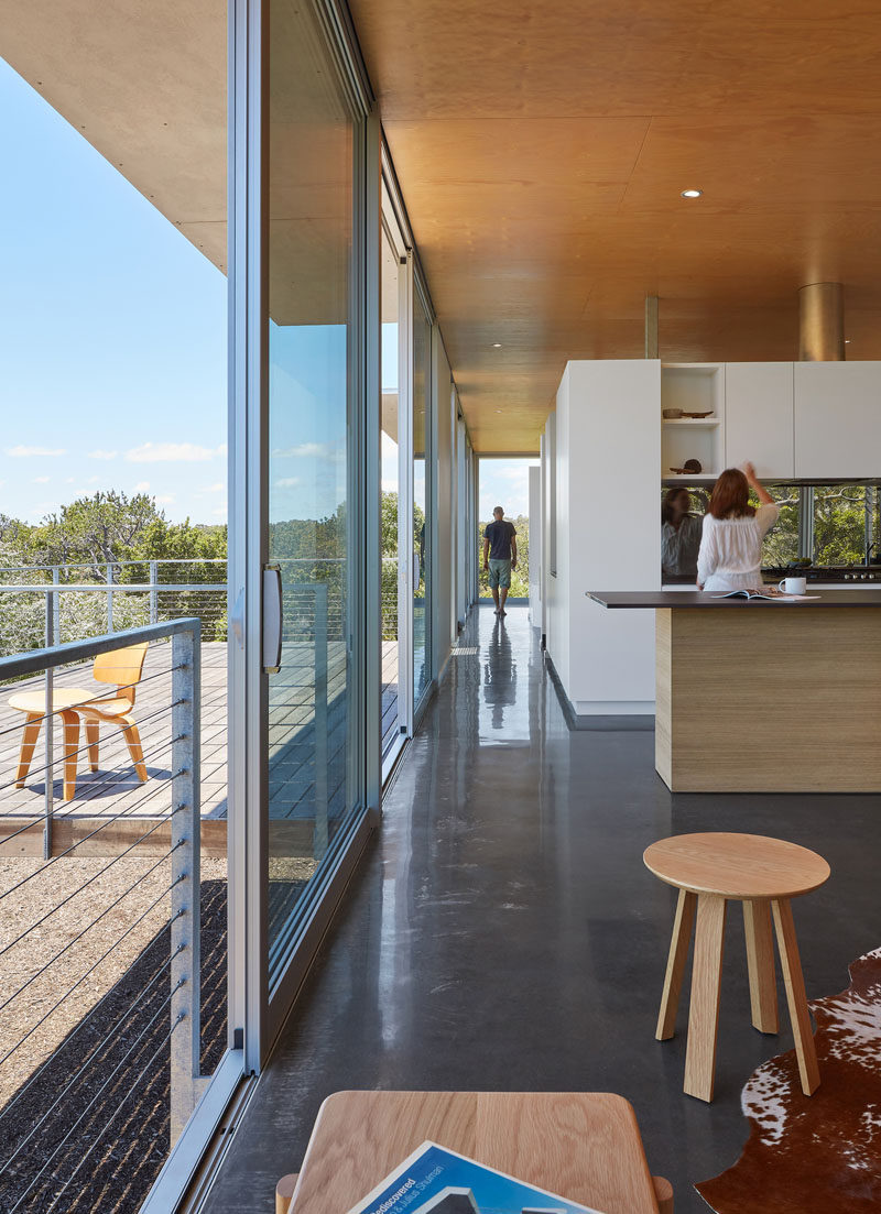 The service zone of this modern house, encompassing kitchen, laundry, bathroom and robe as well as a study are grouped in a centrally located 'pod', with the walls stopping short of the ceiling to enhance the visual flow of one space into another. #Architecture #ModernHouse #InteriorDesign